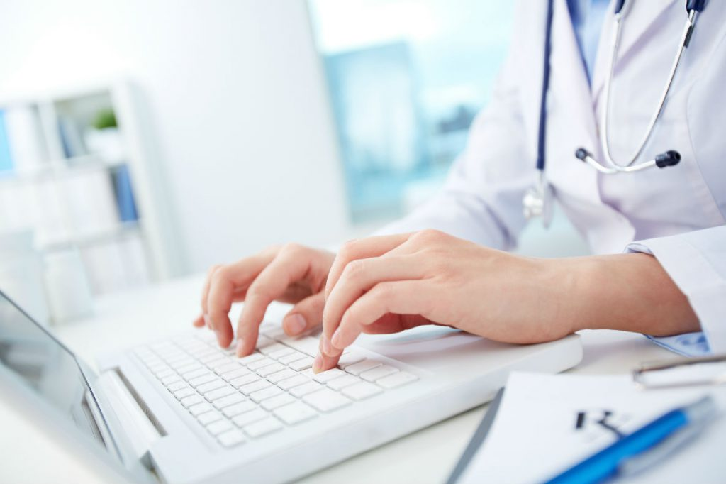 A doctor is typing on a laptop.